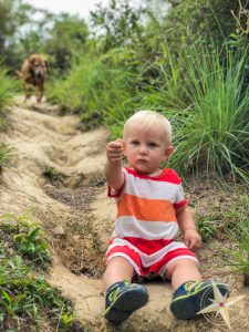 Man Cheung Po-babys first hike 2018- baby sitting on dirt with dog behind him