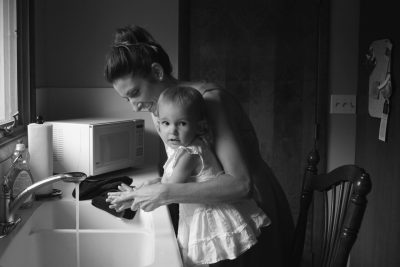 Mother washing child's hands