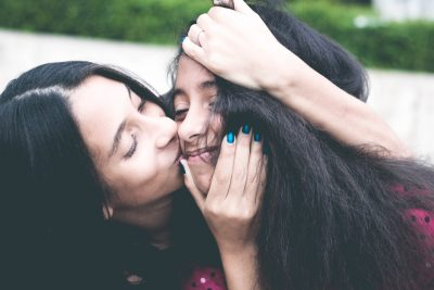 mother kissing teen daughter