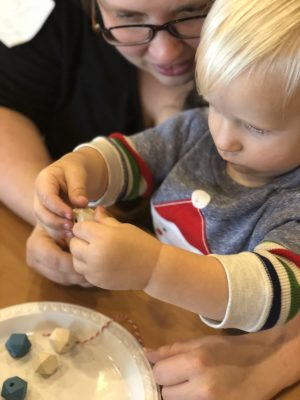 toddler using fine motor skills to thread a bead on a wire