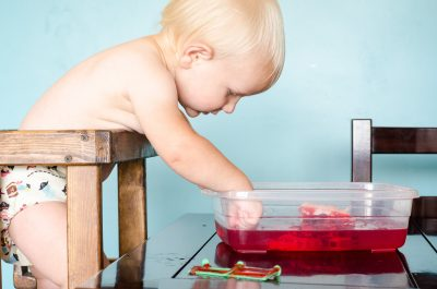 toddler hesitantly playing in jello while wearing a cloth diaper | This Indulgent Life